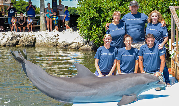 Six team members at the Dolphin Research center pose with a dolphin while modeling their Academy T-shirts.