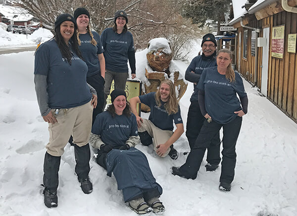 Seven staff modeling Academy T-shirts in the snow.